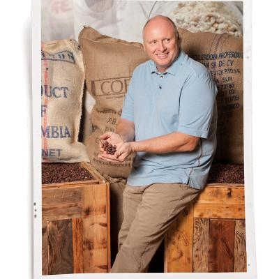 Richard Foley at his bean-to-bar chocolate factory, with crates of cacao beans from Central and South America; ChocXO chocolates, sold at  his Irvine factory,  and his Costa Mesa and Lake Forest cafes.