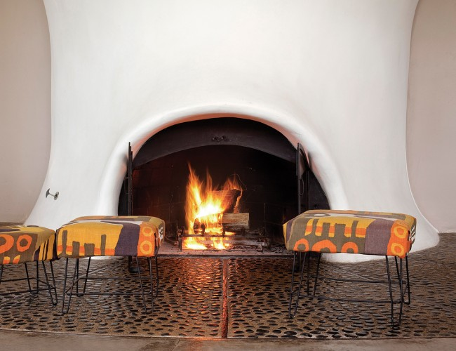 Stools sit atop a radiating pebble floor in front of the hearth.