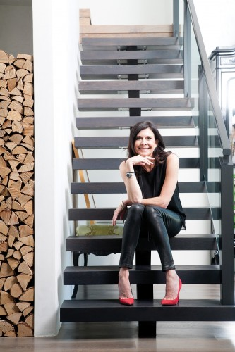 Designer Melissa Palazzo on her charcoal-stained white oak stairs; a tall stack of firewood is both functional and graphic.