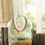 French wine vessel adorned with African glass bead necklaces