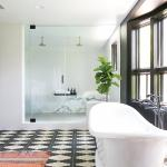 A spacious, free-standing tub rests on dramatic black-and-white tiles from Exquisite Surfaces in Laguna Niguel. Photo by Ryan Garvin.